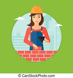 Bricklayer with spatula and brick - A female bricklayer in...
