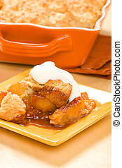 Peach cobbler served with whipped cream