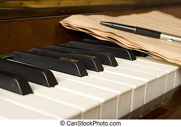 Piano with notes - Brown wooden piano with music books and...