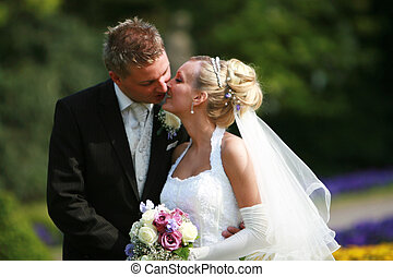 Young couple -  bride and bridegroom - kissing - outside