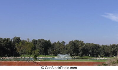 Moroccan golf course from car - Small lake with fountain on...