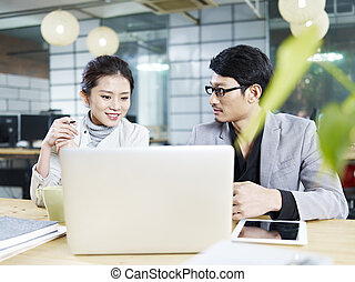 asian business man and woman working together in office -...