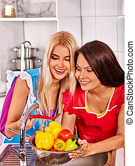 Women washing vegetables at kitchen - Two young woman friend...