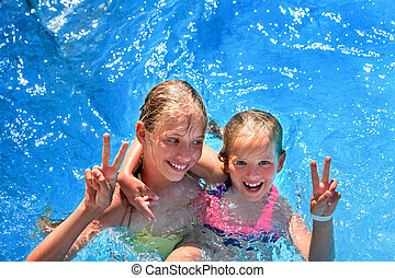 Child on water slide in aquapark. - Two children in swimming...