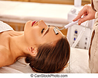 Young woman receiving electric facial massage - Young woman...