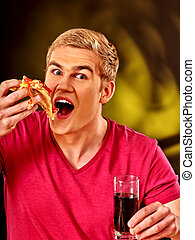 Young man eating slice of pizza .