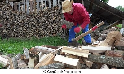 worker gather to the arms chopped firewood in country yard...