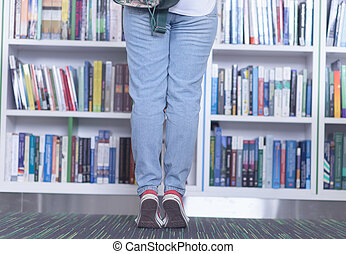 female student selecting book to read in library - smart...