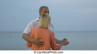 Slow dance on the sea shore - Senior couple enjoying slow...