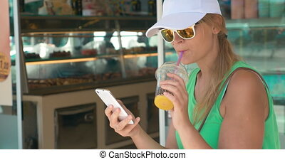 Woman using phone in street on summer day - Young woman in...