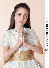 Pretty girl on the day of their communion in prayer with the...
