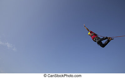 Man jumping off a cliff - A man jumps from a cliff into the...