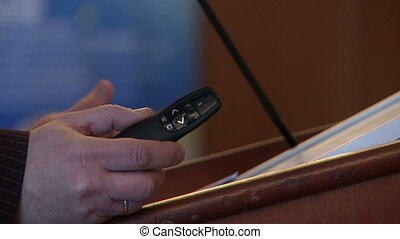 View of speakers hand with remote control, close-up