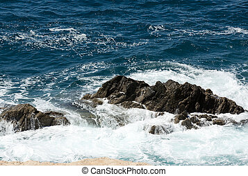Wave splashing over a rock on Caleta Negra beach in Ajuy on...