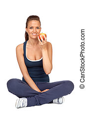 Gymnastics girl with an apple sitting with cross-legs on...
