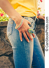 summer trendy bijou - woman hand on blue jeans with big...