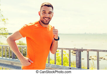smiling young man running at summer seaside - fitness,...