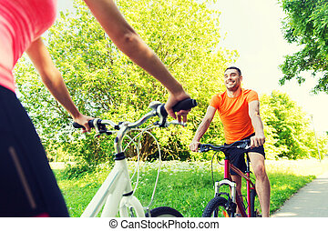 close up of happy couple riding bicycle outdoors - fitness,...