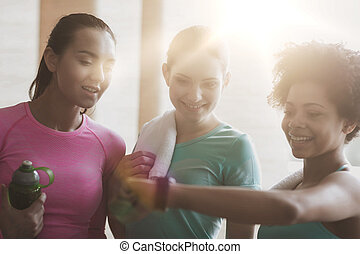 happy women showing time on wrist watch in gym - fitness,...