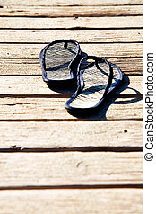 Flipflops - Black summer sandals on the sandy dock