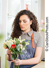 Focused woman florist working and making flower bouquet in...