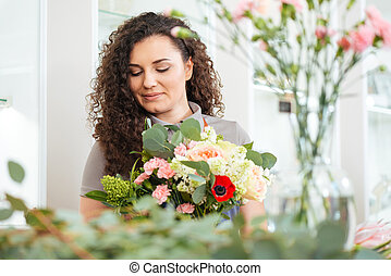 Lovely woman florist with bouquet of flowers working in shop...