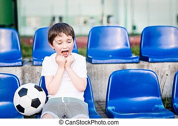 Little football fan happy after a goal for his favorite team