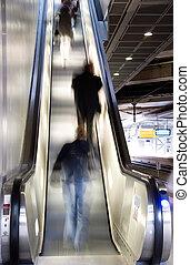 people on escalator - blurred people on an escalator in a...