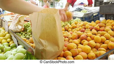 Buyer Putting Apricots into Paper Bag - Paper bag is...