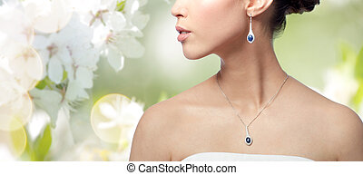 close up of woman with earring and pendant - beauty,...