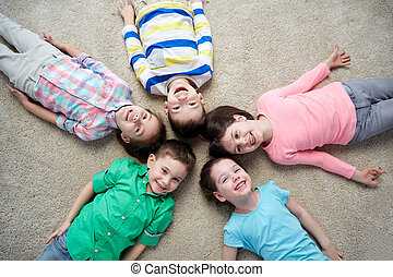 happy smiling little children lying on floor - childhood,...