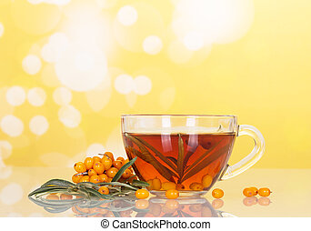 Buckthorn berries and cup tea on abstract yellow background...