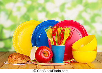 Bright disposable tableware, croissant and  apple on  abstract green background.