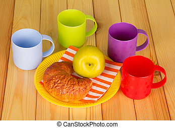 Bright cups and disposable plate with croissant , apple. -...