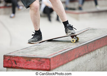 Skater grinding on a ledge in skatepark