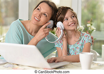 woman and little girl listening music - Middle-aged woman...