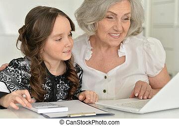 little girl making homework with granny - Cute little girl...