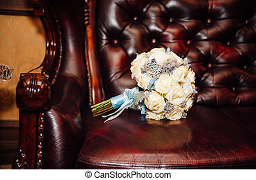 beautiful bridal bouquet of roses on brown chair