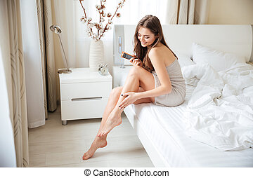 Woman applying cream on legs - Charming woman applying cream...