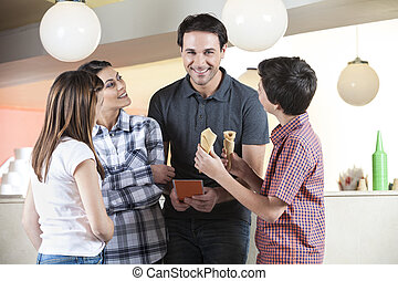 Family Looking At Mid Adult Man Holding Menu - Happy family...