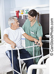 Smiling Man Being Assisted By Nurse In Using Zimmer Frame -...
