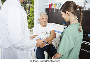 Patient Looking At Nurse While Doctor Holding Clipboard -...