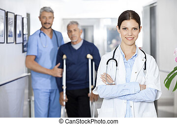 Female Doctor Standing With Colleague And Senior Patient In...
