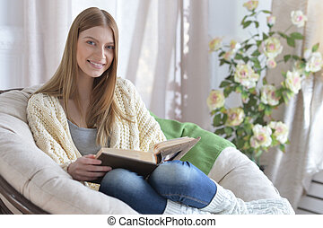 Woman reading a book in cozy armchair - Young attractive...