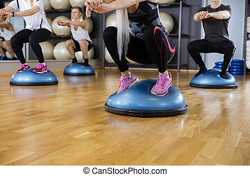 Friends Performing Squatting Exercise On Bosu Ball In Gym -...