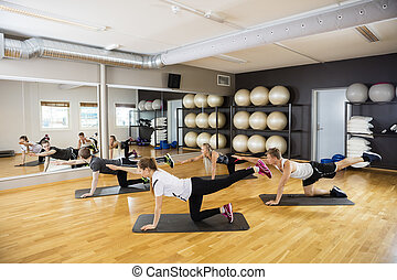 Friends Performing Yoga In Gym