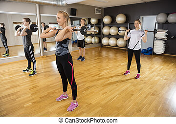 Friends Lifting Barbells While Standing In Fitness Club -...