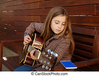 blond kid girl learning play guitar with smartphone winter...