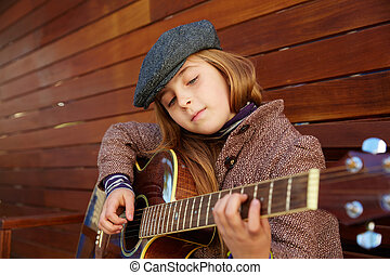 blond kid girl playing guitar with winter beret and coat on...