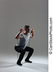 Fitness man squatting with expander - Full length portrait...
